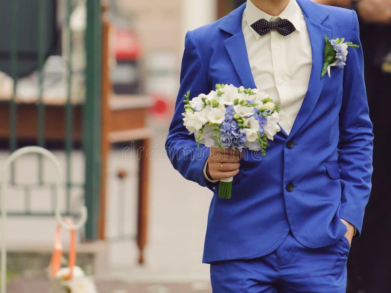 Bruidegom met boeket stock afbeelding
