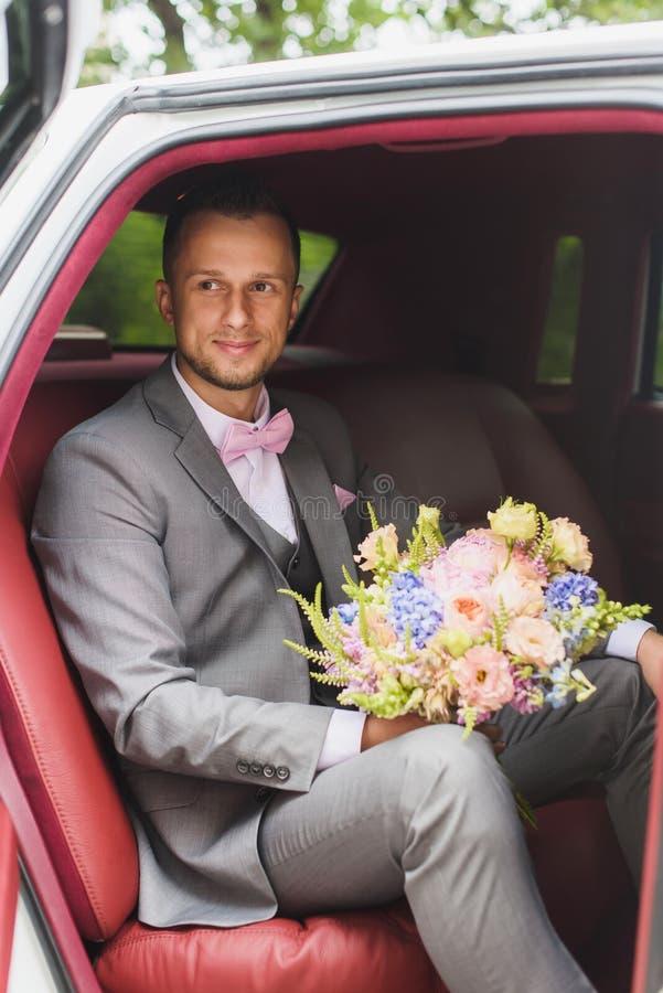 Bruidegom met boeket in de huwelijksauto royalty-vrije stock fotografie