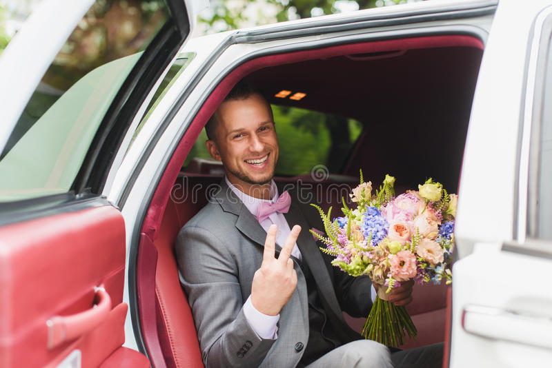 Bruidegom met boeket in de huwelijksauto royalty-vrije stock afbeeldingen