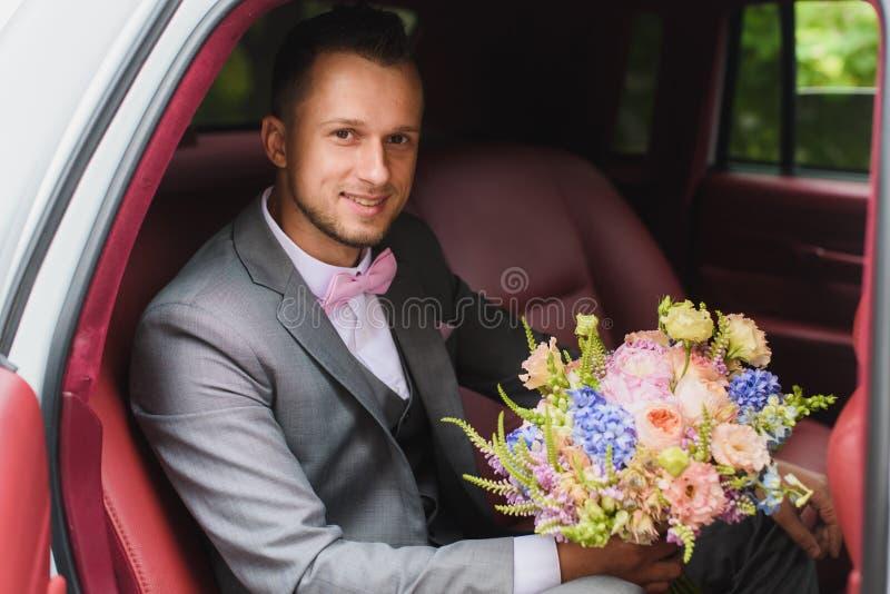Bruidegom met boeket in de huwelijksauto stock foto's
