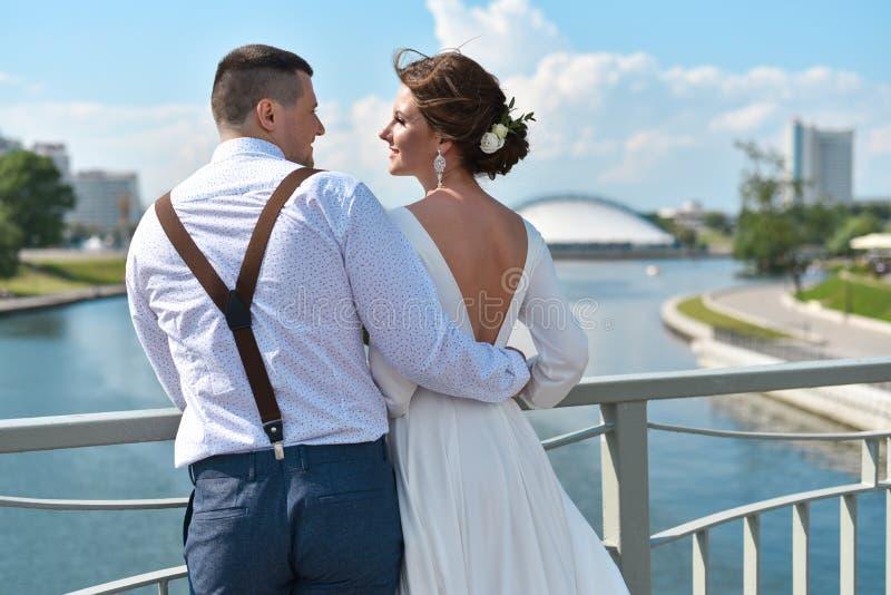 Bruidegom met de bruid op de brug in de stad royalty-vrije stock foto's