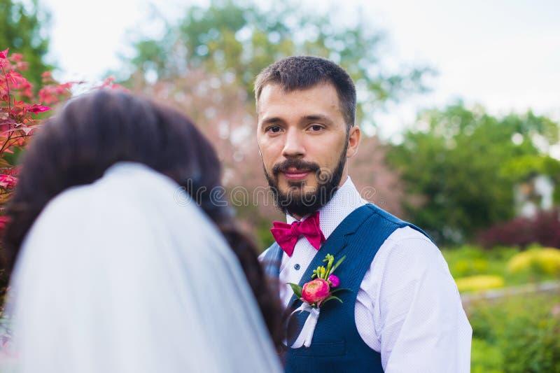 Bruidegom met een baard die haar bruid bekijken royalty-vrije stock fotografie