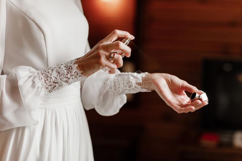 Bruidhanden die parfum op haar pols toepassen, close-up selectieve nadruk royalty-vrije stock fotografie