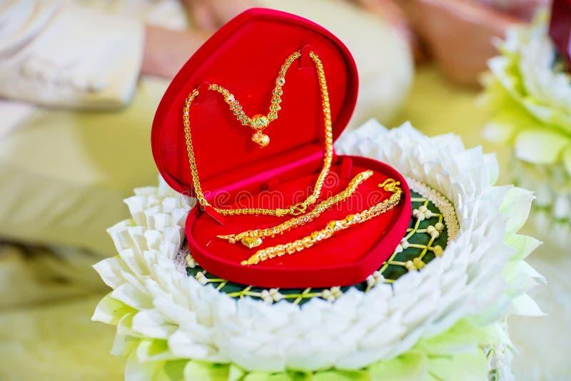 Bruidprijs, gouden halsband en gouden armband op delukeplaat in Thaise huwelijksceremonie stock foto's