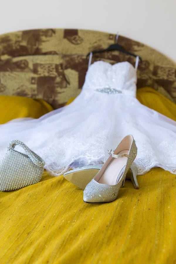 Bruidrobe en alle toebehoren in bed stock afbeeldingen