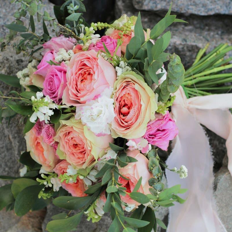 Bruids boeket die op de stenen liggen Het huwelijksboeket van perzikrozen door David Austin, roze enig-hoofd nam aqua, eucalyptus royalty-vrije stock afbeeldingen