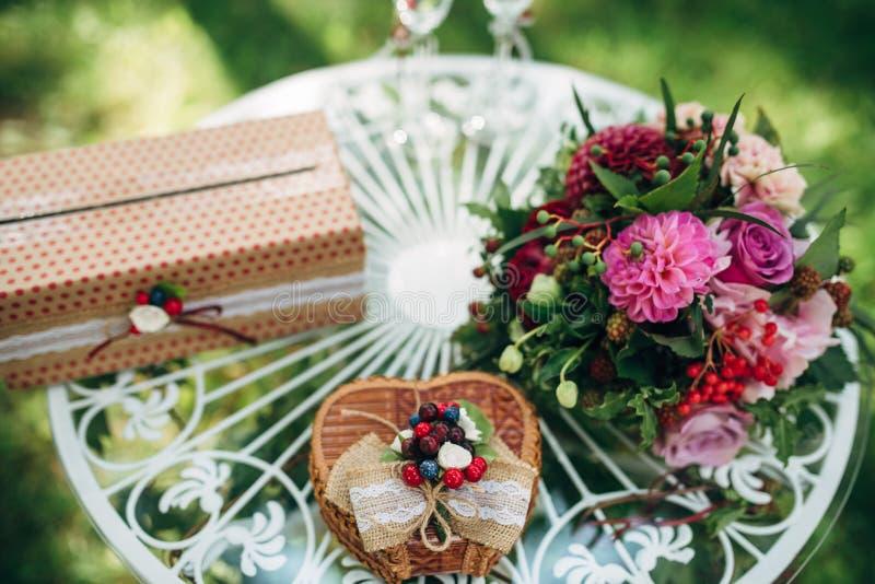 Bruids boeket met roze en purpere bloemen, twee glazen op witte rondetafel royalty-vrije stock afbeelding