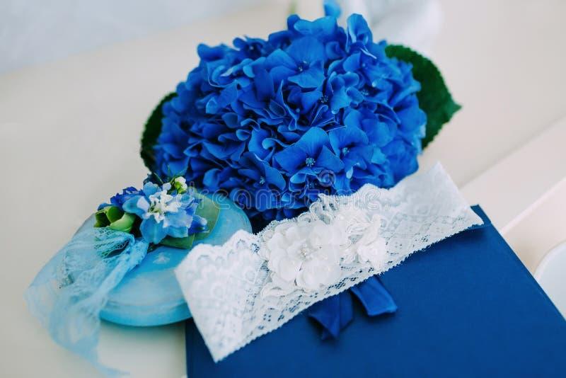 Bruids kouseband op een blauwe tribune, met blauwe hydrangea hortensia's op achtergrond Huwelijk kunstwerk stock foto