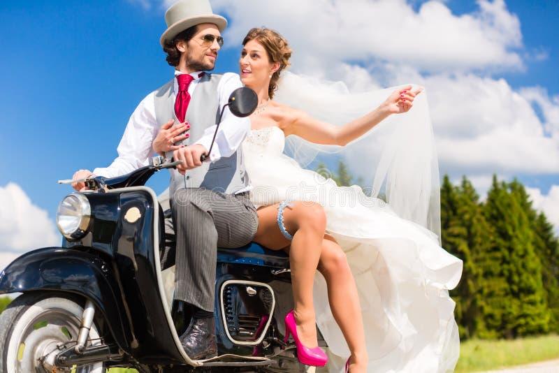 Bruids paar drijfscooter die toga en kostuum dragen stock foto