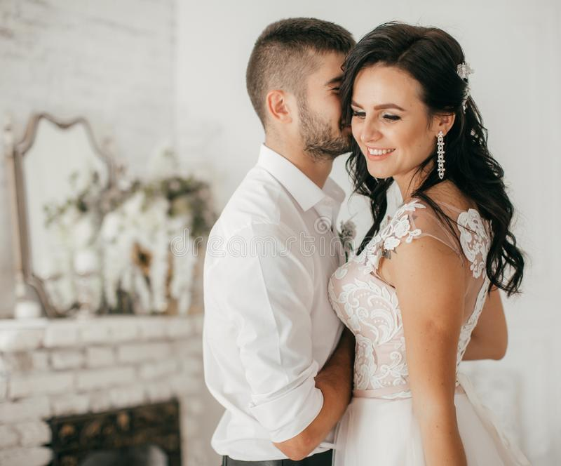 Bruids paar, Gelukkige Jonggehuwdevrouw en man die binnen aan de slaapkamer omhelzen stock foto's