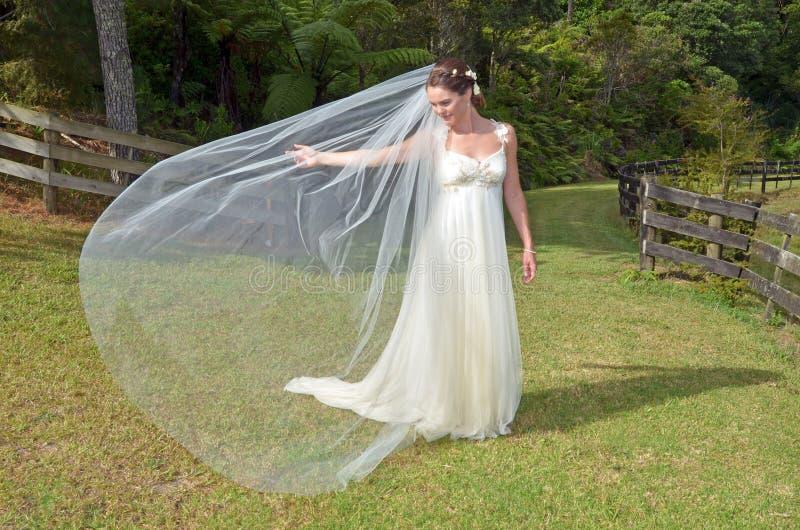 Bruids spel met haar sluier openlucht op haar Huwelijksdag royalty-vrije stock fotografie