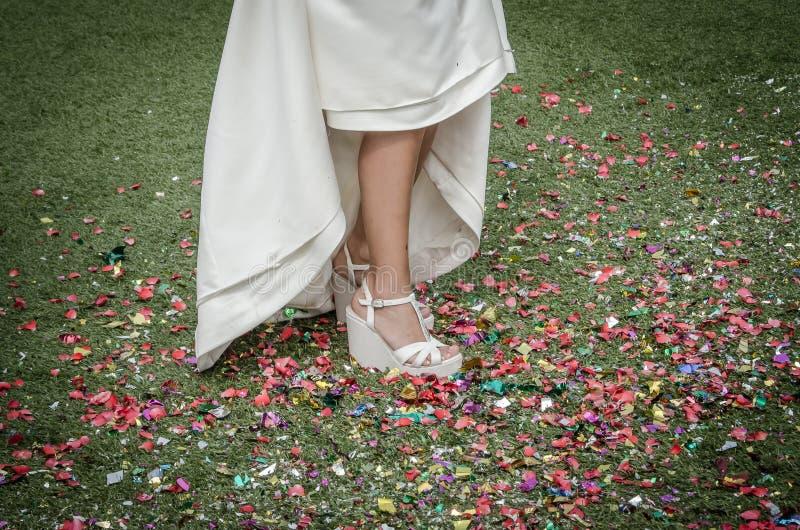Bruidschoenen die op confettien op de vloer stappen stock foto