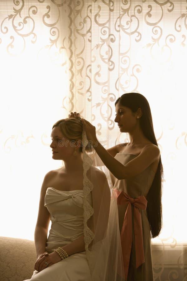 Bruidsmeisje dat sluier plaatst. stock afbeelding