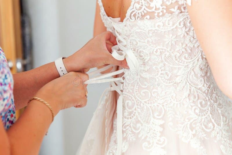 Bruidsmeisje die bruid helpen het rijgen van haar huwelijks witte kleding vóór ceremonie vastmaken stock foto's