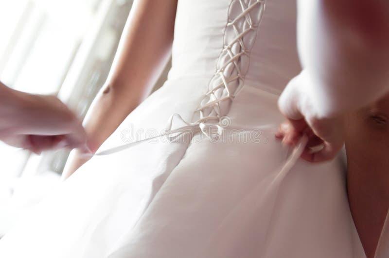 Bruidsmeisje die bruid helpen knopen op korset vastmaken en haar kleding krijgen royalty-vrije stock afbeelding