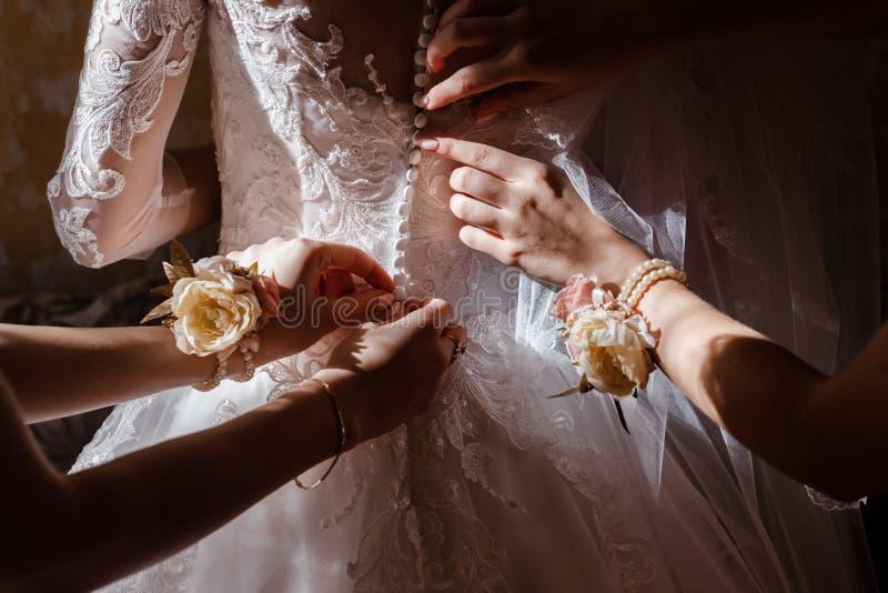 Bruidsmeisje die bruid helpen korset vastmaken en haar kleding krijgen, die bruid in ochtend voorbereiden op de huwelijksdag stock foto's
