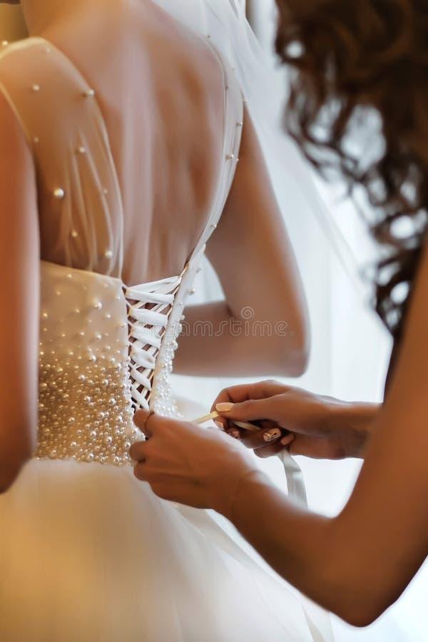 Bruidsmeisje die bruid helpen korset vastmaken en haar kleding krijgen, die bruid in ochtend voorbereiden op de huwelijksdag stock afbeelding