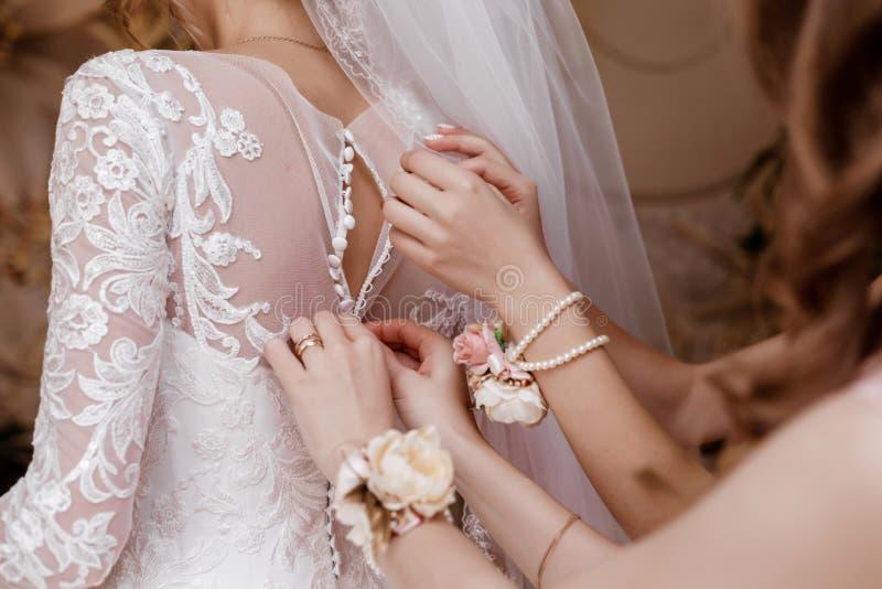 Bruidsmeisje die bruid helpen korset vastmaken en haar kleding krijgen, die bruid in ochtend voorbereiden op de huwelijksdag stock fotografie