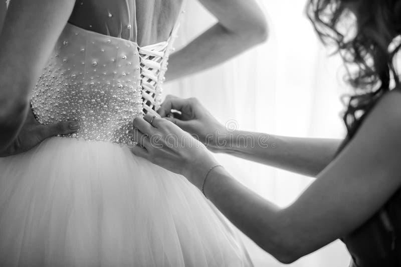 Bruidsmeisje die bruid helpen korset vastmaken en haar kleding krijgen, die bruid in ochtend voorbereiden op de huwelijksdag royalty-vrije stock foto's
