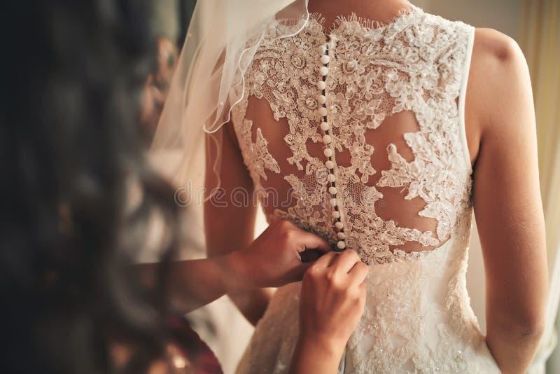 Bruidsmeisje die bruid helpen korsetclose-up vastmaken en haar kleding, voorbereidingsconcept in ochtend krijgen voor huwelijksda stock foto's