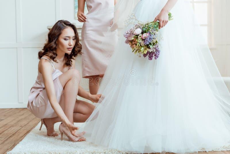 Bruidsmeisje die bruid voor ceremonie voorbereiden stock afbeelding