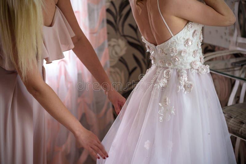 Bruidsmeisje die bruid voorbereiden op de huwelijksdag de hulp maakt een huwelijkskleding de bruid vóór de ceremonie vast Luxe br stock foto