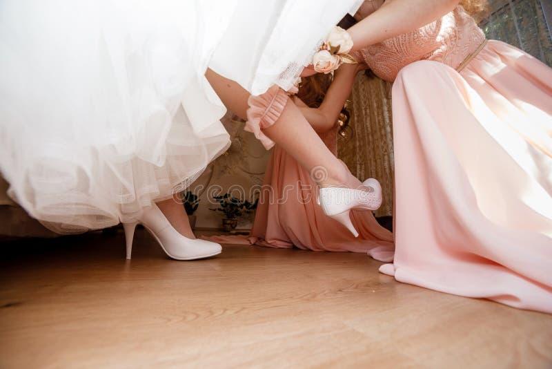 Bruidsmeisje die bruid voorbereiden op huwelijksdag het Bruidsmeisje helpt haar om vulling-juwelen op haar been te dragen royalty-vrije stock afbeelding