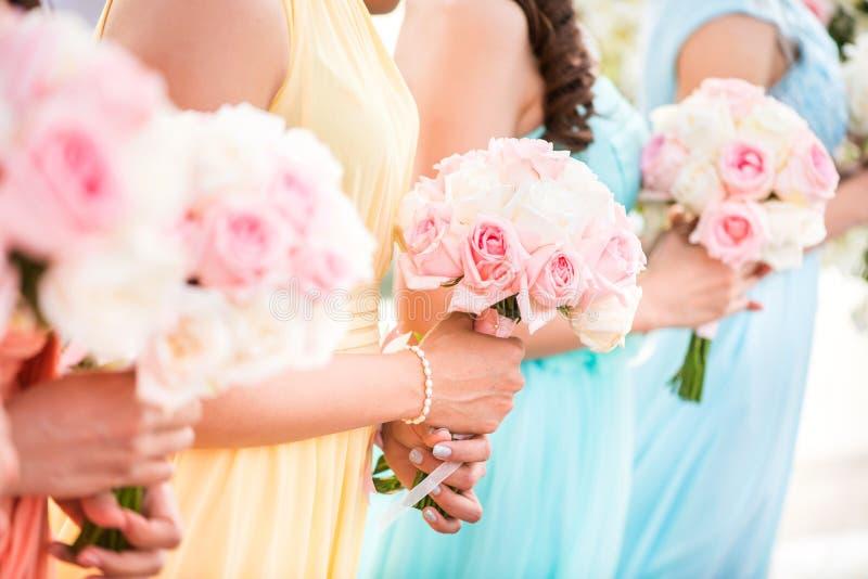 Bruidsmeisje die een boeket van rozen houden bij het huwelijk stock foto