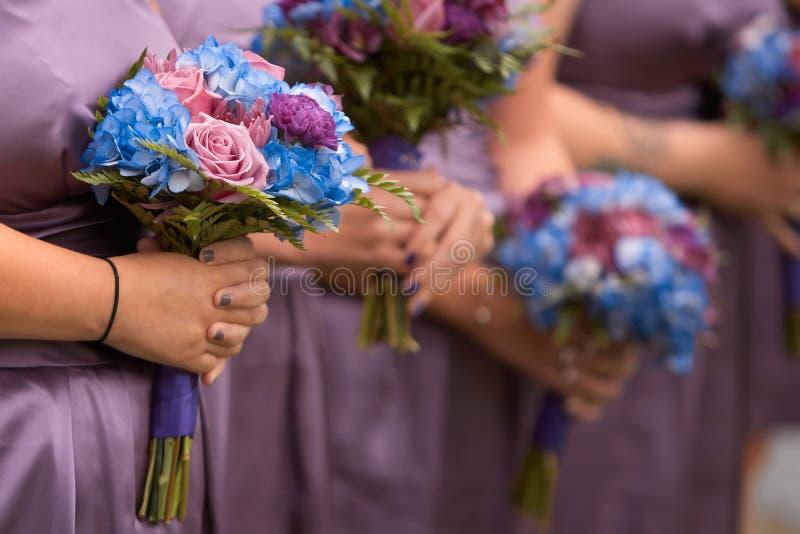 Bruidsmeisjes die boeketten houden stock afbeeldingen