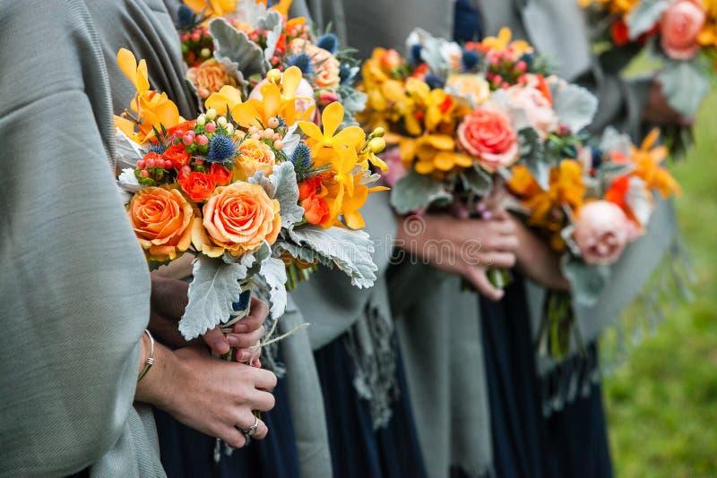 Bruidsmeisjes die hun huwelijksboeketten van bloemen met gele, rode, blauwe en oranje bloemen houden stock afbeelding
