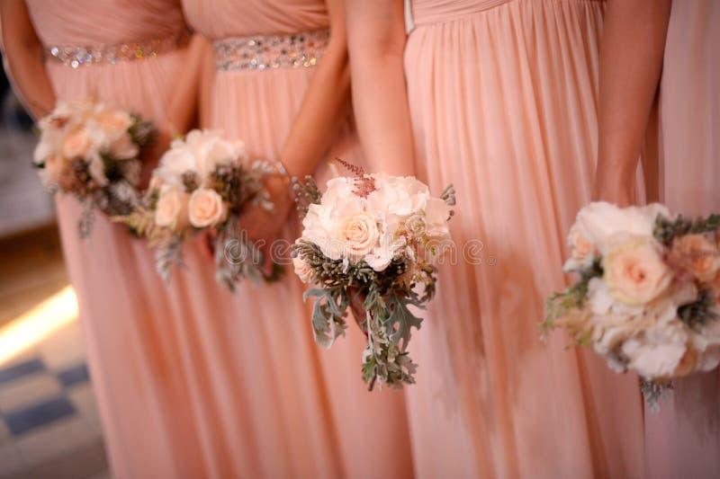 Bruidsmeisjes die mooie bruids boeketten houden royalty-vrije stock afbeeldingen