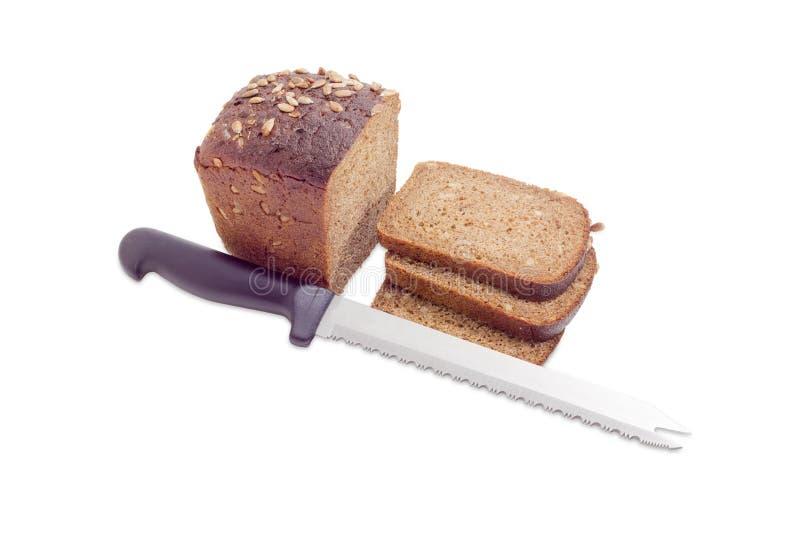 Bruin brood met korrel van zonnebloemen en keukenmes royalty-vrije stock foto's