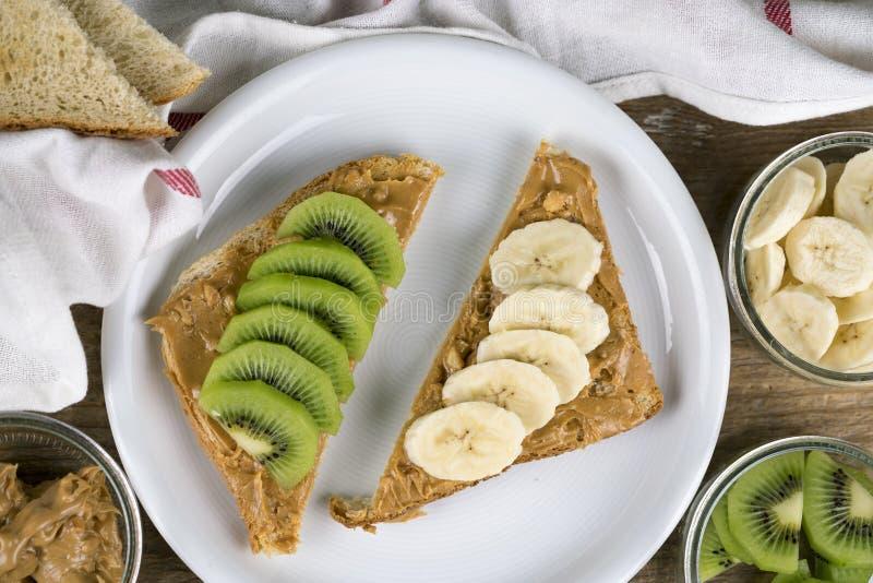 Bruin brood met pindakaas en fruit stock fotografie