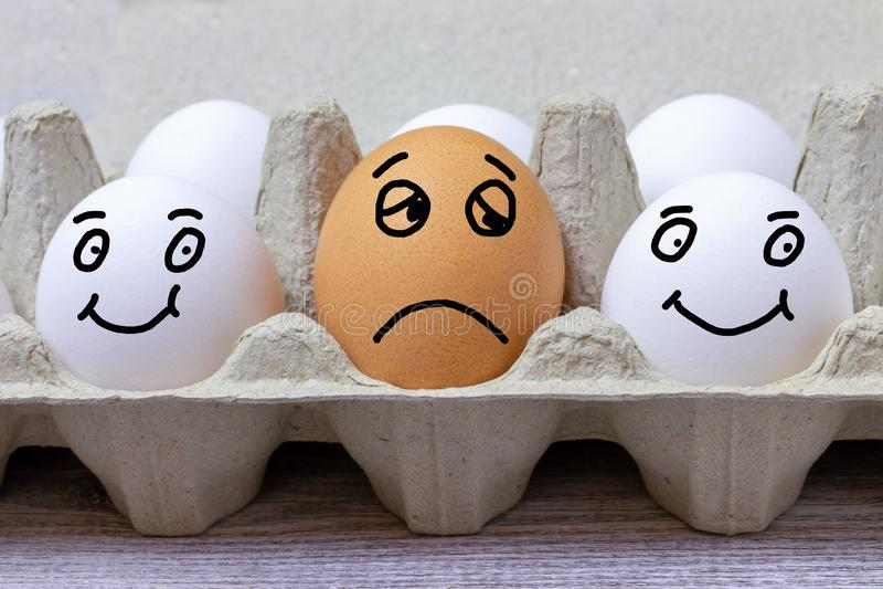 Bruin ei met gezichtsuitdrukking van droevig tussen twee witte gelukkige eieren stock foto