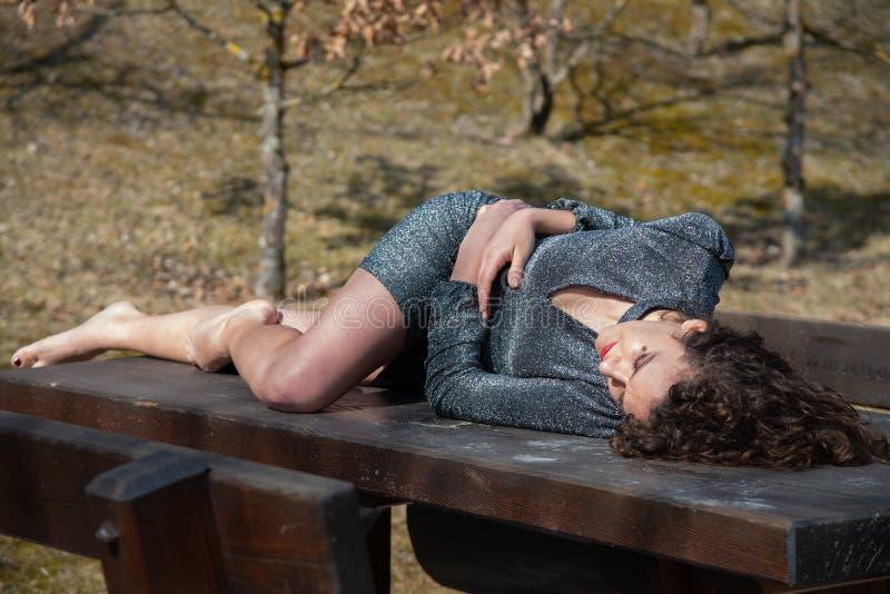 Bruin golvend, blootvoets haarmeisje, die op een stevige houten lijst in de bergen liggen stock afbeelding
