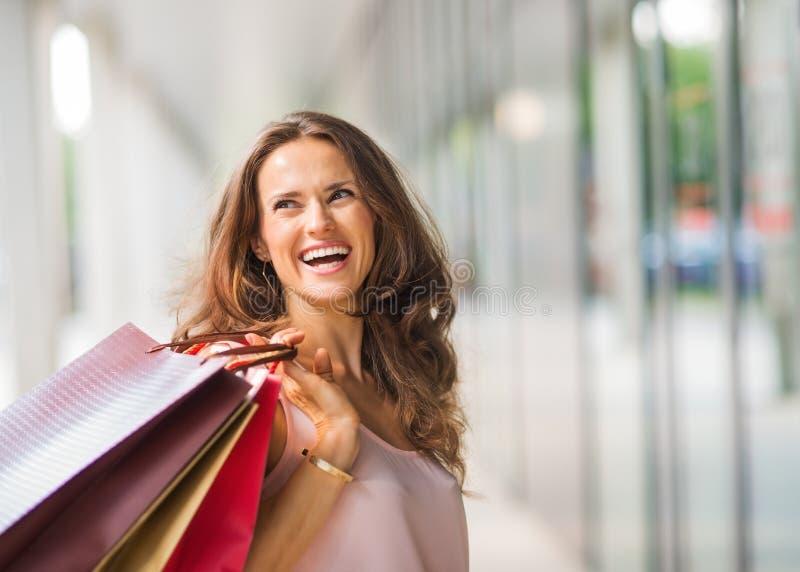 Bruin-haired, gelukkige, glimlachende vrouw die het winkelen zakken steunen stock afbeeldingen