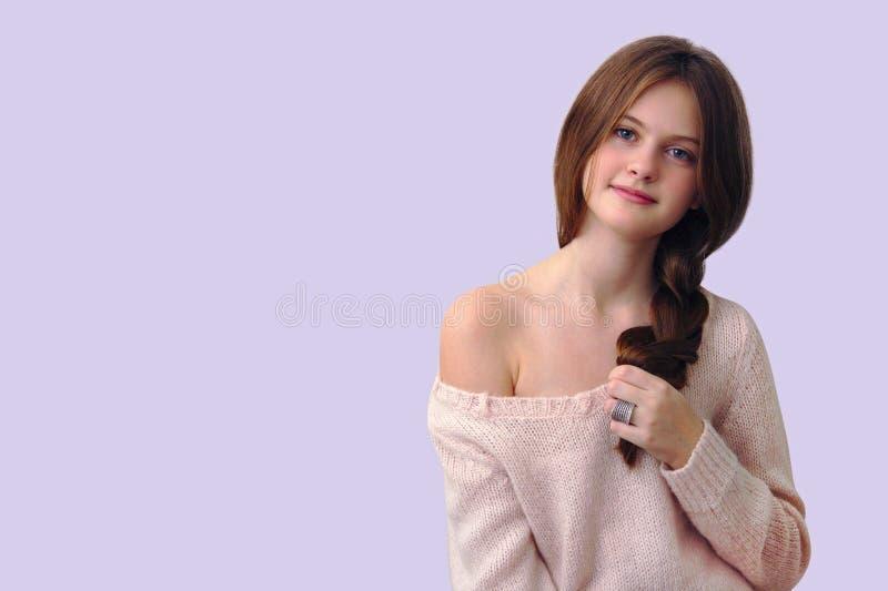 bruin-haired schuw meisje die een vlecht in zijn hand op een roze achtergrond houden royalty-vrije stock foto