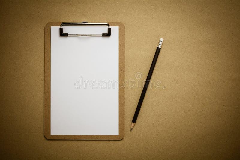 Bruin klembord en Witboekblad op bruine gerecycleerde document achtergrond royalty-vrije stock foto's
