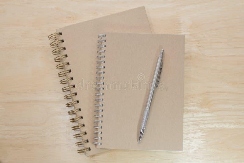 Bruin notitieboekje twee en potlood metaal stock fotografie
