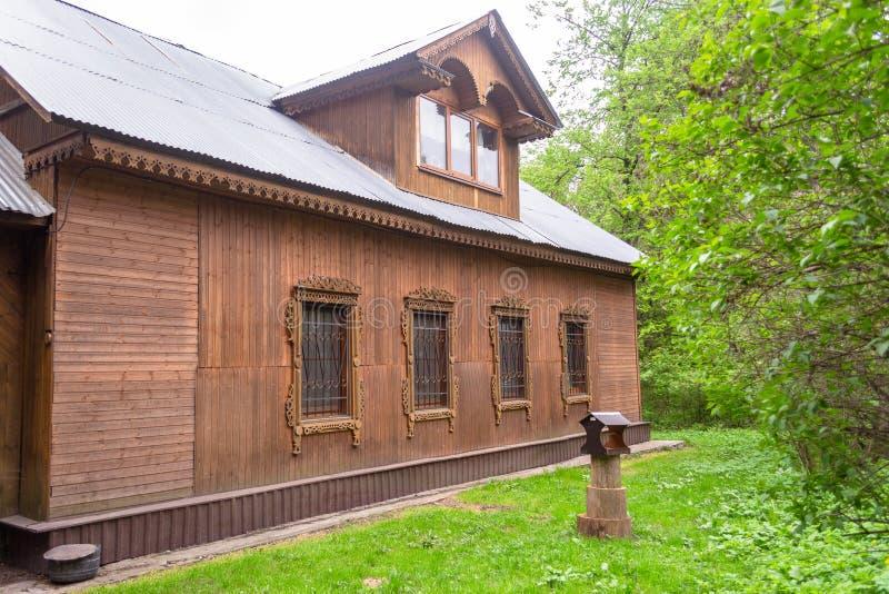Bruin oud rustiek één-verhaal huis, met gesneden platbands op de vensters stock fotografie