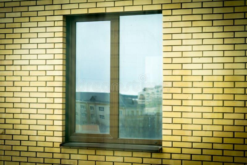 Bruin plastic venster in een baksteenhuis royalty-vrije stock foto's
