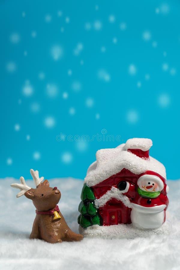 Bruin rendier die op de sneeuw dichtbij Sneeuwman en rode huis en Kerstboom situeren royalty-vrije stock fotografie