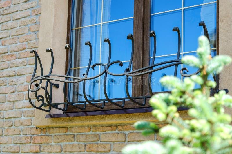 Bruin venster met gestileerd ijzernetwerk stock foto's