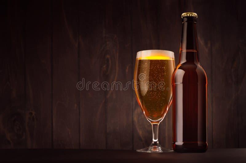 Bruine bierfles en glastulp met gouden omhoog lagerbier op donkere houten raad, exemplaarruimte, spot stock foto's