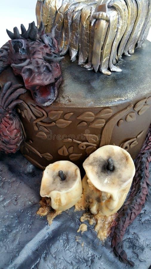 Bruine cake met model van een rode draak en kaarsen stock foto