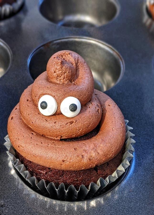 Bruine cupcake met het suikerglazuur van pooemoji royalty-vrije stock afbeeldingen