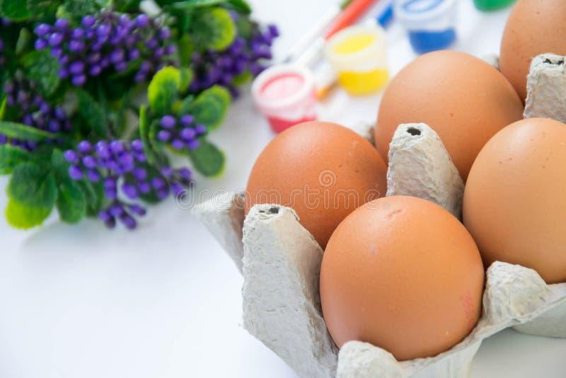 Bruine de kippeneieren van Pasen in kartoncontainer, met plastic bloemen en vage verven, kleurrijk palet op de achtergrond, verf stock fotografie