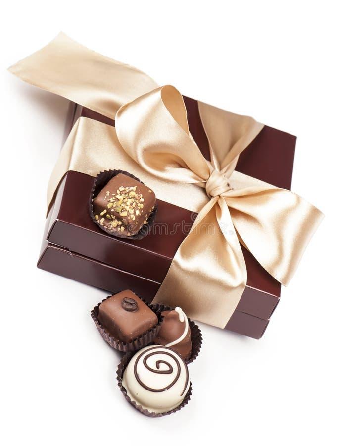 Bruine doos met suikergoed en gouden band stock afbeeldingen