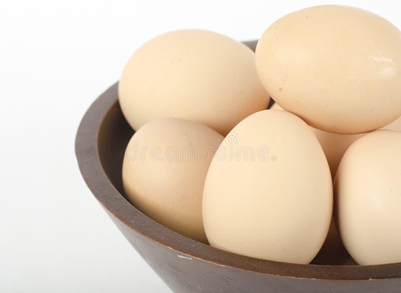 Bruine eieren in een houten kom royalty-vrije stock afbeeldingen