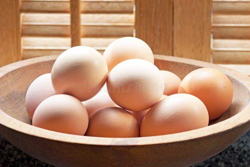 Bruine Eieren in Houten Kom stock foto